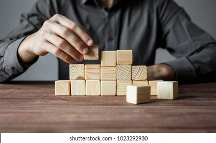 Closeup of businessman making a pyramid with empty wooden cubes. Concept of business hierarchy and business strategy.