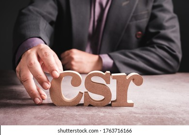 Closeup businessman place a wood alphabets on the desk as the abbreviation of CSR, CSR or Corporate Social Responsibility, concept