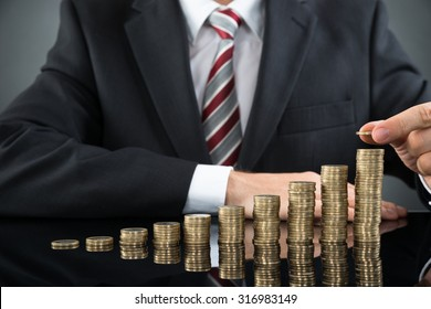 Close-up Of Businessman Placing Coin Over Stack Of Coins At Desk