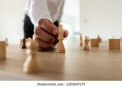 Closeup of businessman positioning king chess figure in the center of other figures placed on office desk.