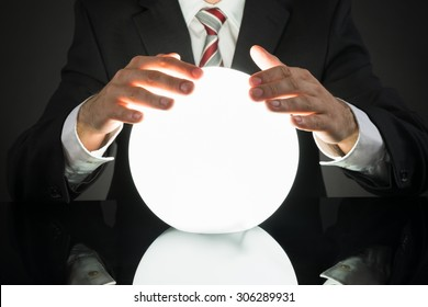Close-up Of Businessman Predicting Future With Crystal Ball At Desk