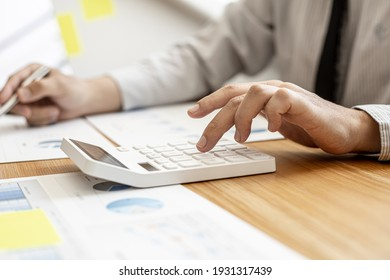 Close-up businessman pressing a calculator to calculate numbers from the company's financial documents prepared by the Finance Department for a meeting with business partners. Financial concept.