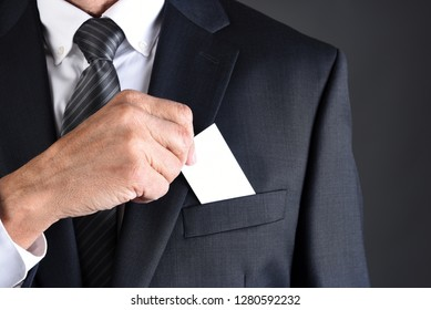 Closeup of a businessman putting a blank business card into his jackets breast pocket. Man is unrecognizable.