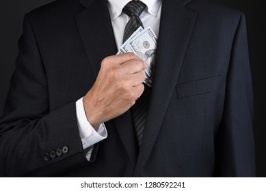 Closeup of a businessman putting hundred dollar bills into his jackets breast pocket. Man is unrecognizable.