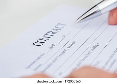 Close-up Of A Businessman Reading Contract Paper