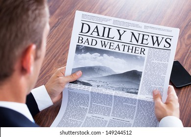 Close-up Of Businessman Reading Weather News On Newspaper