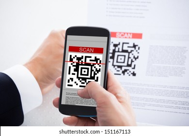 Close-up Of Businessman Scanning A Barcode Using Cell Phone