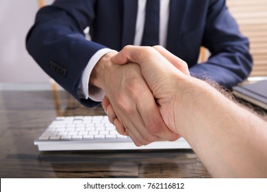 Close-up Of A Businessman Shaking Hand With His Partner In Office