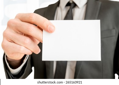 Closeup of businessman showing blank white business card with copy space ready for contact info or other company information.