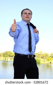 Closeup of businessman showing ok with focus on a hand at nature background