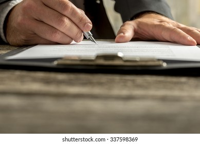 Closeup of businessman signing contract, document or legal papers clipped on clipboard with fountain pen.