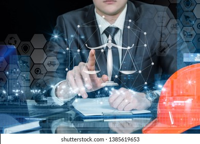A closeup of a businessman sitting at the table and operating with the comb financial system of icons and symbols and juridical scales. The concept of legal and faithful investments.