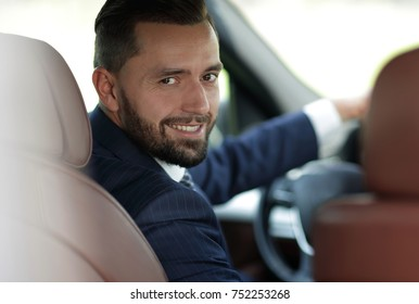 Close-up of a businessman sitting at the wheel of a car