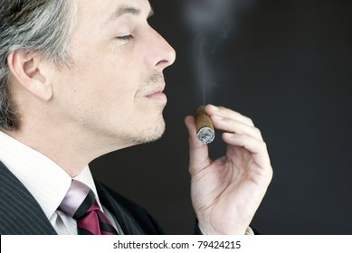Close-up of a businessman smelling a cigar, side view.