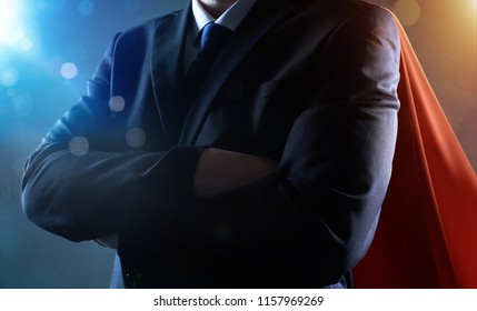 Closeup Businessman in suit and cape hero with crossed arms . bokeh and light flare effect apply .