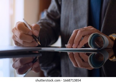 Closeup businessman in suit hand sign and write documents on the desk at office.