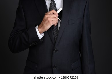 Closeup of a businessman taking his smart phone from his inside suit jacket pocket.