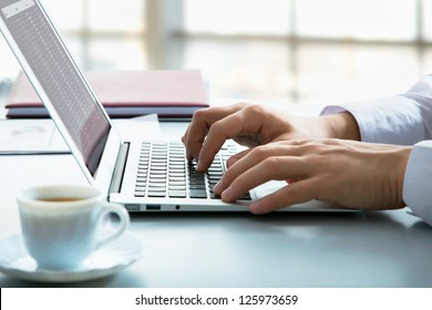 Closeup of businessman typing on laptop computer