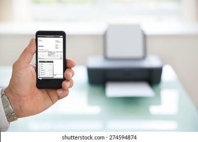 Close-up Of A Businessman Using Cellphone For Printing Invoice. Photographer owns copyright for images on screen