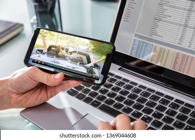 Close-up Of Businessman Watching Video On Mobilephone While Working In Office