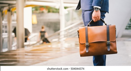 Closeup Of A Businessman wear the watch and Holding leather Briefcase Going To Work with the sunshine