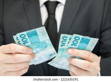 Close-up businessman wearing black suit and tie holding Brazilian money notes. Brazil one hundred (100) reais. Selective focus.