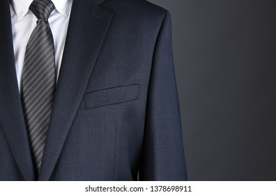 Closeup of a businessman wearing a Charcoal Gray Suit with white shirt and Striped tie.