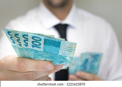 Close-up businessman wearing white shirt and black tie holding Brazilian money notes. Brazil one hundred (100) reais. Selective focus.