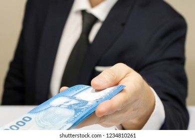 Close-up businessman wearing white shirt and black tie receiving chilean money notes. Chile ten thousand (10000) pesos. Selective focus.