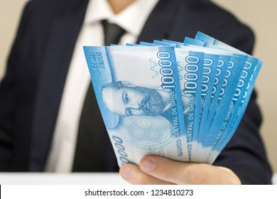 Close-up businessman wearing white shirt and black tie holding chilean money notes. Chile ten thousand (10000) pesos. Selective focus.