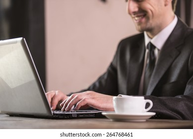Close-up. Businessman working at laptop with cup of coffee.