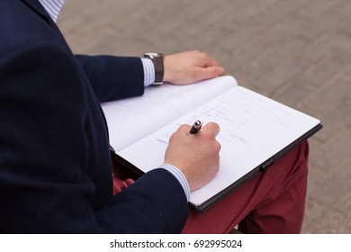 Close-up of a businessman writing in a notebook. Man's hands working.