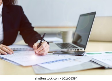 Close-up of businessman writing paper on wooden desk in office.