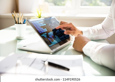 Close-up of a businessman's hand analyzing graph on laptop at workplace