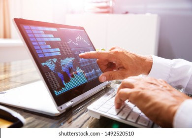 Close-up Of A Businessman's Hand Analyzing Graph On Laptop