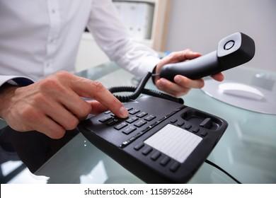 Close-up Of A Businessman's Hand Calling On Landline