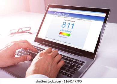 Close-up Of A Businessman's Hand Checking Credit Score On Laptop
