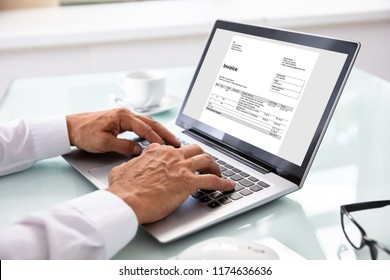 Close-up Of A Businessman's Hand Checking Invoice On Laptop