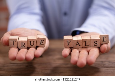 Close-up Businessman's Hand Holding True And False Blocks Over Wooden Desk