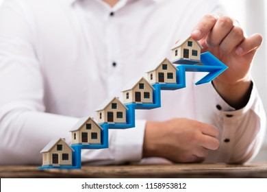 Close-up of a businessman's hand placing house models on increasing blue arrow staircase