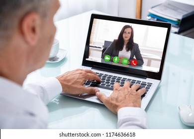 Close-up Of A Businessman's Hand Videoconferencing With Female Colleague On Laptop