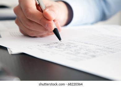 Closeup of a businessman's hand while writing some documents