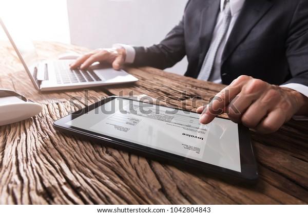 Nahaufnahme der Hand eines Geschäftsmanns, der mit Rechnungen auf digitalen Tablet-Computern arbeitet