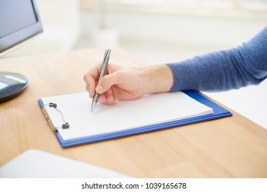 Close-up of businessman's hand writing something on the paper. Casual professional man sitting at desk and fill the form.