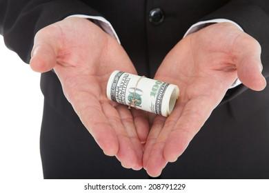 Closeup of businessman's hands holding tied dollar bills