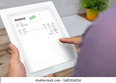 Close-up of businessman's hands working on invoice on tablet calculating Tax at desk in office