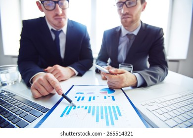 Close-up of businessmen analyzing chart at meeting