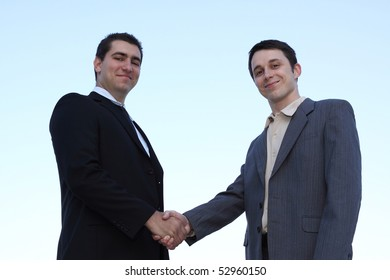 Closeup of businessmen shaking hands over a deal on sky background