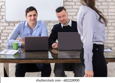 Close-up Of Businessmen Using Laptop Looking At Woman In Office