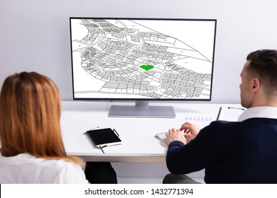 Close-up Of A Businesspeople Analyzing Cadastre Map On Computer In The Office